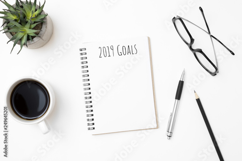 Photo  Notebook with 2019 Goals text on top of white office desk table with supplies
