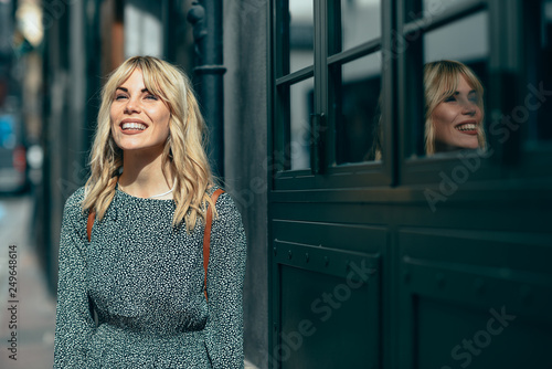 Fotografia, Obraz  Smiling young blonde woman standing on urban background.