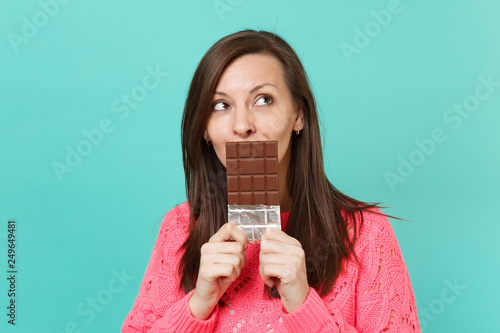 Fotografie, Tablou  Pensive young woman in knitted pink sweater looking up, hold in hand, covering mouth with chocolate bar isolated on blue wall background, studio portrait