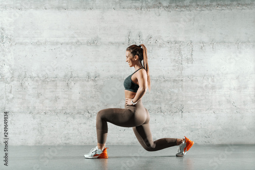 Canvas Print Side view of smiling sporty Caucasian woman dressed in sportswear and with ponytail doing lunges in the gym