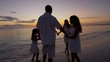 Caucasian family in sunset silhouette outdoor on beach