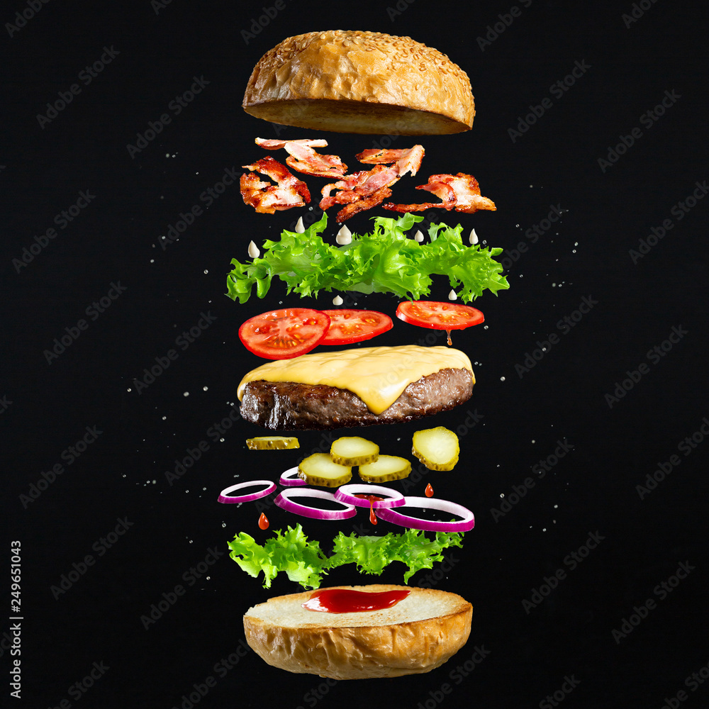 Fototapety, obrazy: Floating burger isolated on black wooden background. Ingredients of a delicious burger with ground beef patty, lettuce, bacon, onions, tomatoes and cucumbers
