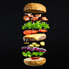 FototapetaFloating burger isolated on black wooden background. Ingredients of a delicious burger with ground beef patty, lettuce, bacon, onions, tomatoes and cucumbers