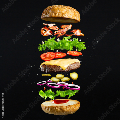 Fototapeta Floating burger isolated on black wooden background. Ingredients of a delicious burger with ground beef patty, lettuce, bacon, onions, tomatoes and cucumbers obraz