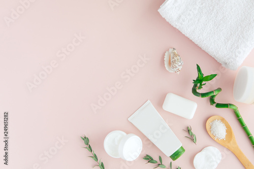 Foto op Canvas Spa Top view of white and green cosmetic set and leaves for facial skin care and spa treatment with bamboo on pink background, flat lay, place for text. Beauty and nature herbal spa concept