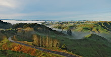 Road Leading Through The Green Hills With Clouds Rolling Over Them During The Sunrise On North Island Of New Zealand.