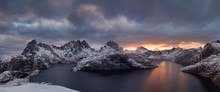 Winter Dramatic Landscape With Snowy Mountains, Sea, Blue And Orange Cloudy Sky Reflected In Water At Sunset. Beautiful Lofoten Islands, Norway. Norwegian Fjords Background. Christmas Time Concept