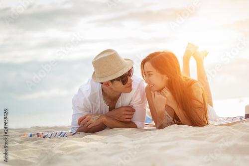 Fotografia  Asian couple lying Honeymoon at sunset