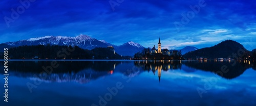 Fotobehang Bergen Beautiful view of famous Bled Island with Catholic Church at scenic Lake Bled with Bled Castle (Blejski grad) and Julian Alps in the background in golden morning light at sunrise in summer, Slovenia