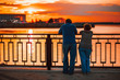 elderly couple standing back on the river bank and watching the sunset