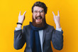Funny bearded businessman making horn gesture - rock and roll sign