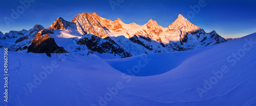 Photo sur Toile Bleu fonce View of snow covered landscape with Dent Blanche mountains and Weisshorn mountain in the Swiss Alps near Zermatt. Panorama of the mountains in Switzerland. Beautiful morning with first snow. Christmas