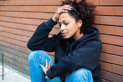 Problematic young woman leaning on brick wall in city street Canvas Print