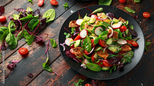 Photographie Traditional fattoush salad on a plate with pita croutons, cucumber, tomato, red