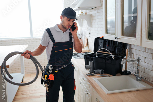 Obraz Busy handyman talk on phone in kitchen. He hold hose. Toolbox on desk. Guy stand at sink. - fototapety do salonu