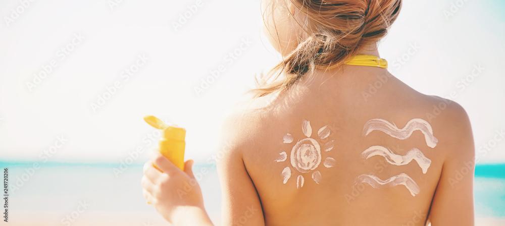 Fototapety, obrazy: child on the beach smears sunscreen. Selective focus.