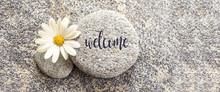 Word Welcome Written On A Stone Background With A Daisy