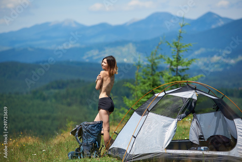 Foto auf Gartenposter Camping Side view of attractive naked female tourist standing near the tent and backpack, enjoying summer morning in the mountains. Camping lifestyle concept adventure vacations outdoor