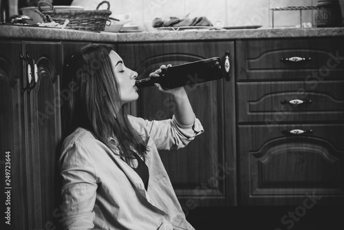 Woman have a depression, problem with alcohol, she sit in a floor in kitchen wit Fototapet