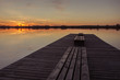 Wooden bridge with planks and sunset over a calm lake