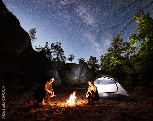 Fototapeta Young couple travellers man and woman resting beside camp, campfire and glowing tourist tent at night. On background beautiful night starry sky full of stars and Milky way, mountain rocks, trees obraz na płótnie