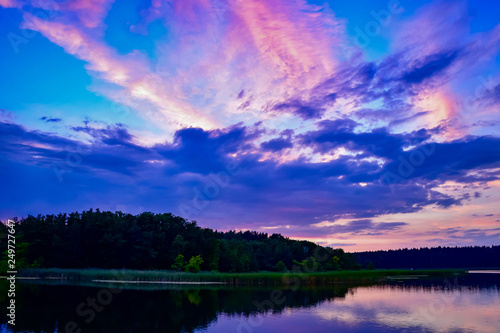 Foto op Plexiglas Donkerblauw Purple and orange sunset over a lake with reflections in the lake