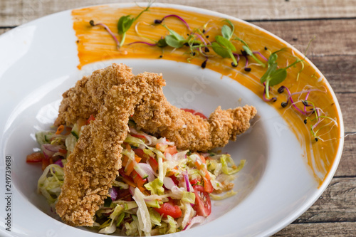 Fototapeta tasty crispy chicken salad appetizer in white plate obraz