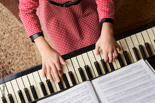 Little girl in red dress performing classical music at home playing the piano looking to the music sheet - 249741688