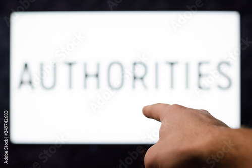 Fotografía  Male`s hand points to tv set with writing AUTHORITIES