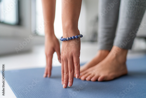 Fototapeta Yoga at home exercise in living room house - woman on fitness mat training stretching legs touching toes