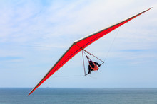 Hang Gliding Man Flying On An Orange Wing At Fort Funston In San Francisco, One Of The Premier Hang-gliding Spots In The Country