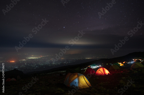 In de dag Kamperen Moshi city by night from a camp on Kilimanjaro slopes