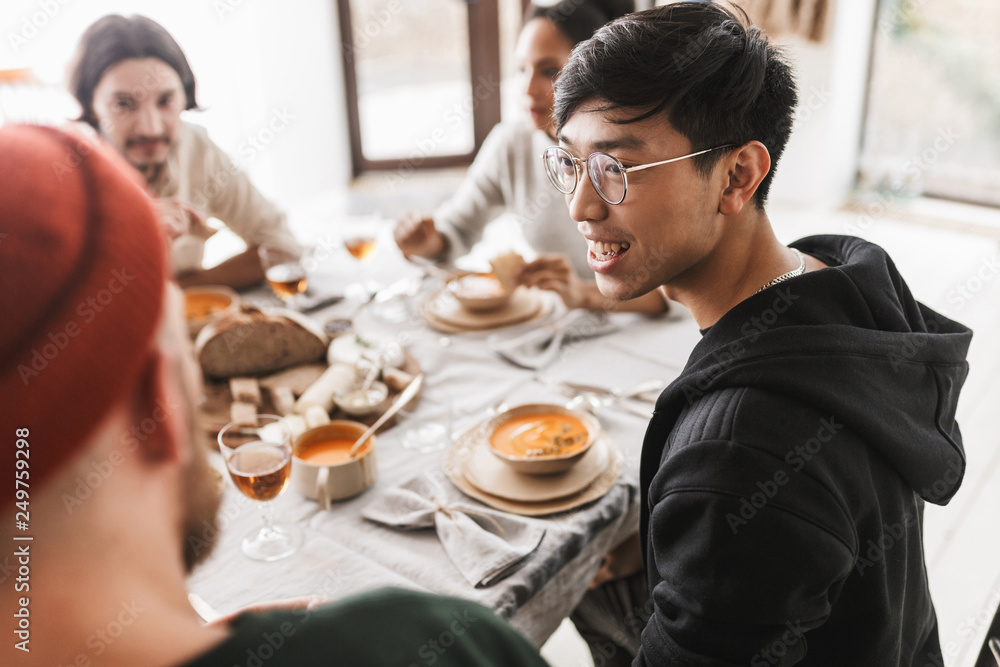 Fototapety, obrazy: Young smiling asian man with dark hair in eyeglasses and hoodie sitting at the table happily looking aside. Group of international friends having lunch spending time together in cozy cafe