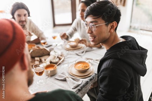 Fotografía  Young smiling asian man with dark hair in eyeglasses and hoodie sitting at the table happily looking aside