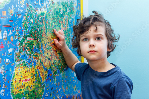 Fényképezés  The curly-headed Child with interest looks at the blue world map
