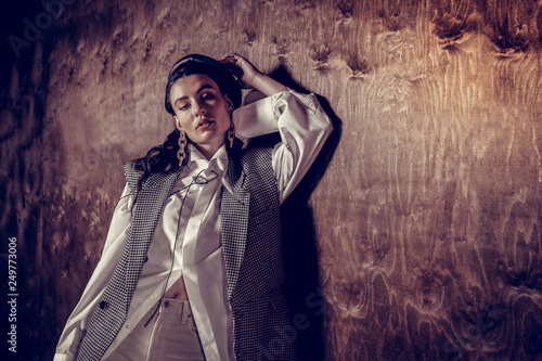 Photo  Attractive stylish young woman touching her cap