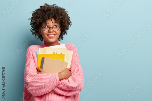 Photo of cheerful pleased schoolgirl looks upwards, dreams about recieving degre Fototapet