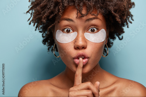 Eye skin treatment  Surprised African American woman applies