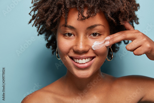 Photo Close up shot of positive dark skinned woman with curly hair, appiles face cream on cheek, poses nude against blue background, cares of beauty, uses cosmetic product