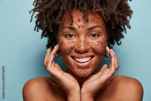 Fototapeta Photo of smiling black woman has cleansing mask or scrub on face, smiles broadly
