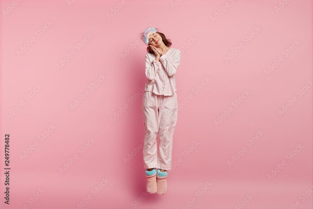 Fototapeta Positive restful lovely woman with eyes shut, enjoys sleeping at home, leans on hands, jumps in air, wears eyemask, nightclothes, domestic shoes, isolated over pink background. Bed time concept