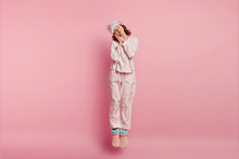 Positive Restful Lovely Woman With Eyes Shut, Enjoys Sleeping At Home, Leans On Hands, Jumps In Air, Wears Eyemask, Nightclothes, Domestic Shoes, Isolated Over Pink Background. Bed Time Concept