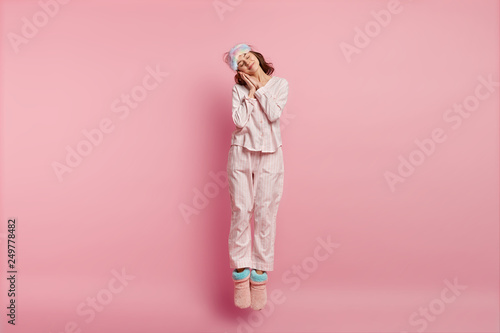 Obraz Positive restful lovely woman with eyes shut, enjoys sleeping at home, leans on hands, jumps in air, wears eyemask, nightclothes, domestic shoes, isolated over pink background. Bed time concept - fototapety do salonu