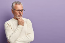 Pensive Pensioner Holds Chin, Being Deep In Thoughts, Tries Find Right Solution, Wears Optical Glasses And Sweater, Isolated Over Purple Background With Copy Space For Your Advertisement Or Text