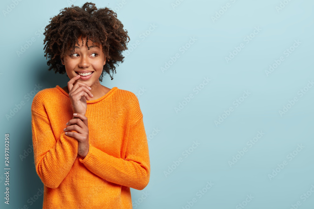 Fototapety, obrazy: Pleased Afro American woman looks aside, keeps hand near mouth, has broad smile, enjoys good moments in life, wears loose orange jumper, isolated over blue background, blank space for your text