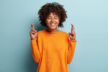 Photo Of Positive African American Woman Has Big Hope, Crosses Fingers, Dressed In Orange Jumper, Believes In Good Fortune, Smiles Broadly, Isolated Over Blue Background. People And Wish Concept