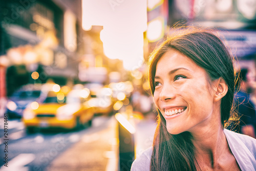 obraz dibond Happy people New York city lifestyle young Asian woman smiling in sunset walking in street with taxi cabs traffic sun shining down in downtown Manhattan, New York City.