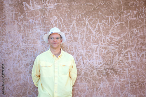 Fotografie, Obraz  Caucasian man standing in front of concrete graffiti wall