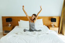 Woman Stretching On Bed In Hotel Room