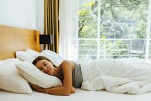Woman Sleeping On Bed In Hotel Room